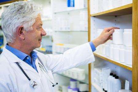 lab coat: Farmac�utico en bata de laboratorio comprobaci�n de los medicamentos en la farmacia Foto de archivo