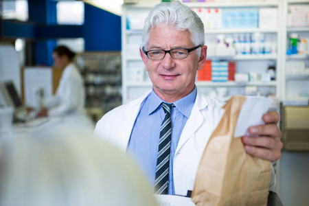 Pharmacist holding a medicine package in pharmacy Stock Photo