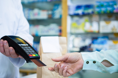Customer taking credit card from payment terminal in pharmacy