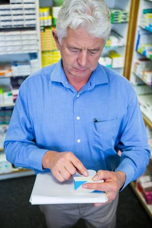salud publica: Farmacéutico comprobación de los medicamentos en la farmacia