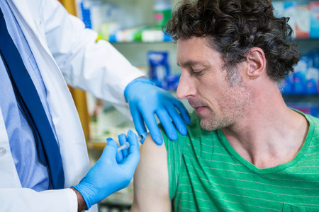 Pharmacist giving injection to patient in pharmacy Stock Photo