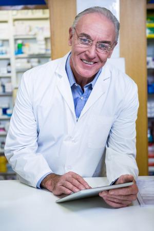 Portrait of pharmacist using a digital tablet in pharmacy