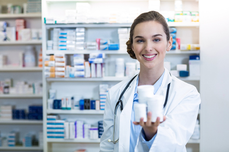 attractive  female: Portrait of pharmacist showing medicine container in pharmacy