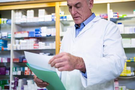 prescriptions: Pharmacist reading prescriptions in pharmacy