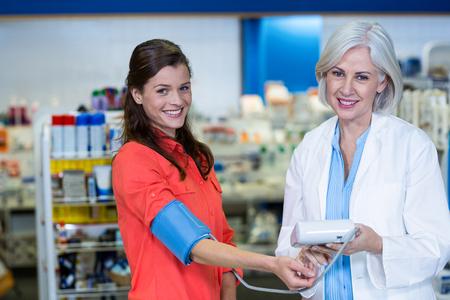 Portrait of pharmacist checking blood pressure of customer in pharmacy