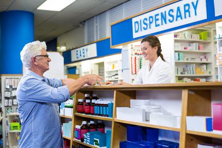 recetas medicas: Pharmacist giving prescriptions of medicine to customer in pharmacy Foto de archivo