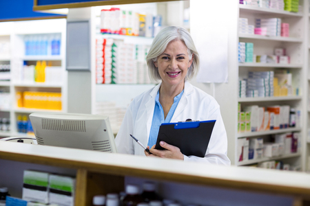 dispensary: Portrait of pharmacist holding a clipboard in pharmacy
