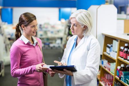 prescriptions: Pharmacist writing prescriptions for customer on clipboard in pharmacy