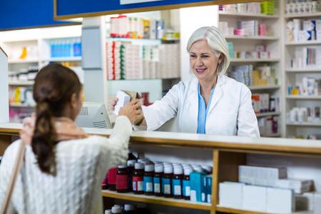 medicine box: Pharmacist giving medicine box to customer in pharmacy Stock Photo