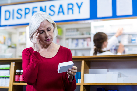 Tensed customer checking a pill box in pharmacy Stock Photo