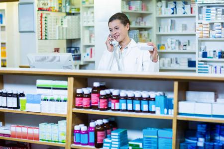 medicine box: Pharmacist holding medicine box while talking on phone in pharmacy