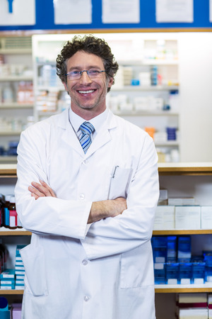 Portrait of pharmacist standing with arms crossed in pharmacy Stock Photo