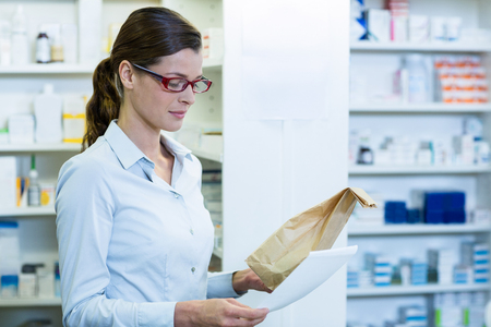 attractive  female: Pharmacist checking prescription and medicine package in pharmacy