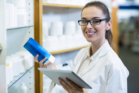 Portrait of pharmacist holding digital tablet while checking medicine in pharmacy Stock Photo