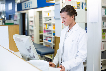 Pharmacist making prescription record through computer in pharmacy