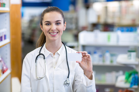 Portrait of female pharmacist holding a pill box in a pharmacy Stock Photo