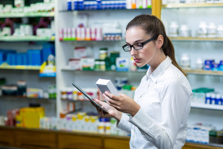 health professional: Pharmacist using digital tablet while checking medicine in pharmacy