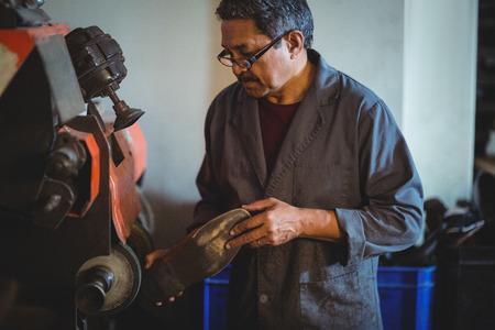 Shoemaker polishing a shoe with machine in workshop Stock Photo - 62471450