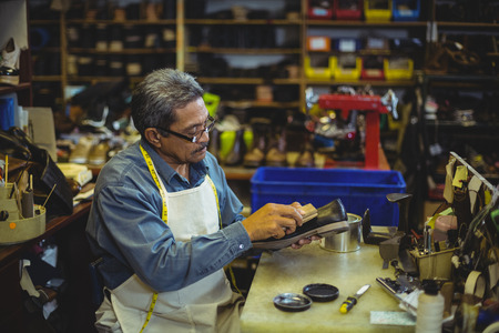 Shoemaker polishing a shoe in workshop