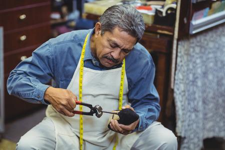 hammering: Shoemaker hammering on a shoe in workshop