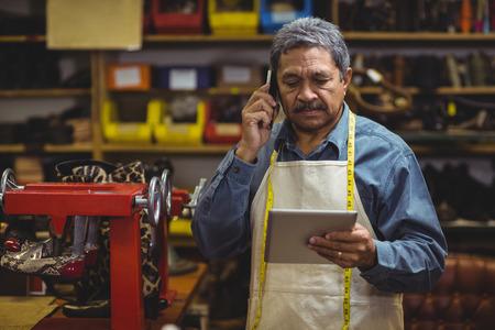 Shoemaker using digital tablet while talking on mobile phone in workshop