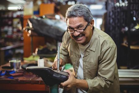 Portrait of smiling shoemaker hammering on a shoe in workshop