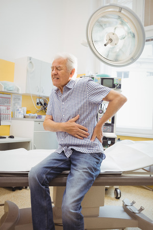 lower back pain: Mature man with lower back pain at the hospital