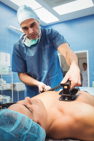 recuperation: Male surgeon resuscitating an unconscious patient with a defibrillator at the hospital Stock Photo