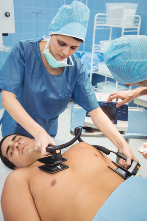 resuscitate: Female surgeon resuscitating an unconscious patient with a defibrillator at the hospital