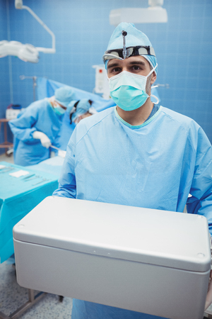 surgical mask woman: Portrait of surgeon holding ice box while colleagues performing operation in operation room