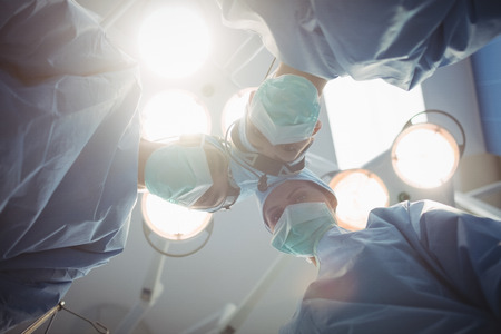surgical tool: Surgeons performing operation in operation room at the hospital Stock Photo