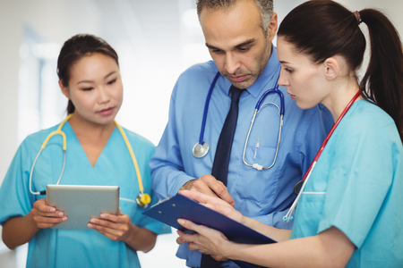 Doctor and nurses looking at clipboard in the hospital