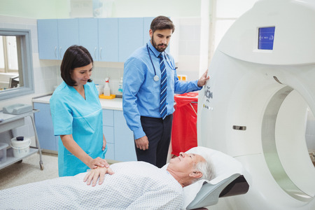 A patient is loaded into an mri machine while doctor and technician watching at the hospital