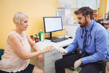 diabetes meter kit: Doctor measuring sugar level of patient with glucometer at the hospital Stock Photo