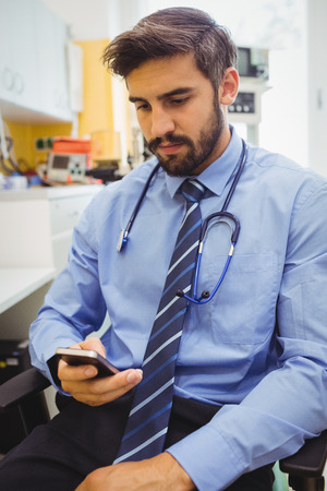 text messaging: Doctor text messaging on mobile phone at the hospital