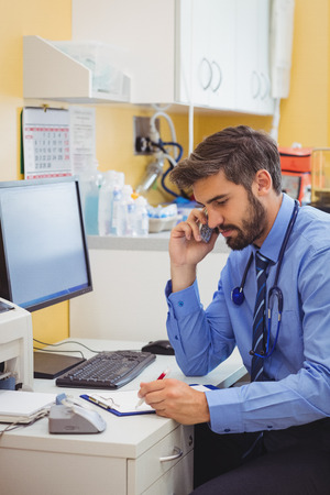 noting: Doctor sitting at his desk and talking on phone at the hospital