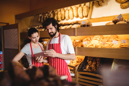 Couple using digital tablet in bakery shop Stock Photo