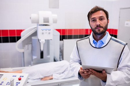 x ray machine: Portrait of doctor holding digital tablet and patient lying on x ray machine in hospital