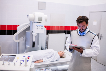 x ray machine: Doctor using digital tablet and patient lying on x ray machine in hospital
