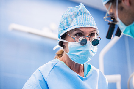surgical mask woman: Surgeons performing operation in operation room at the hospital Stock Photo