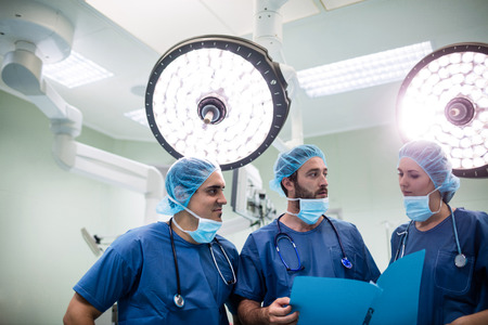operation theatre: Surgeons discussing patient records in operation room at hospital Stock Photo