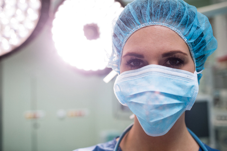 surgical mask woman: Portrait of surgeon wearing surgical mask in operation room at the hospital