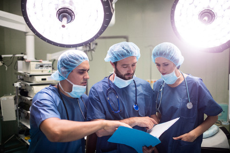 surgical light: Surgeons discussing patient records in operation room at hospital Stock Photo
