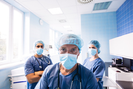 scrub cap: Portrait of surgeon and nurses standing in hospital