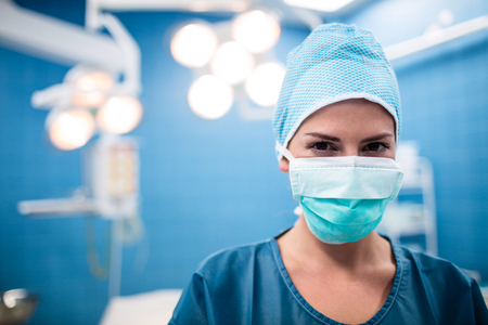 Portrait of surgeon standing in operation room at the hospital Stock Photo