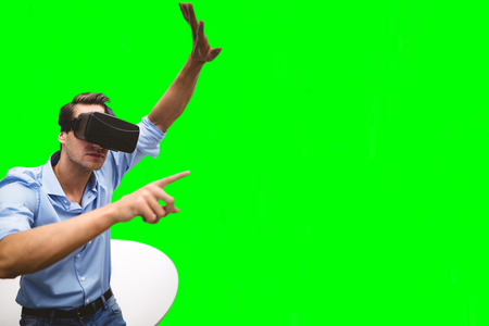 virtual reality simulator: Man pointing while wearing virtual reality simulator against green vignette Stock Photo