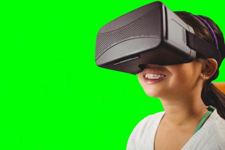Close up of little girl holding virtual glasses against green vignette