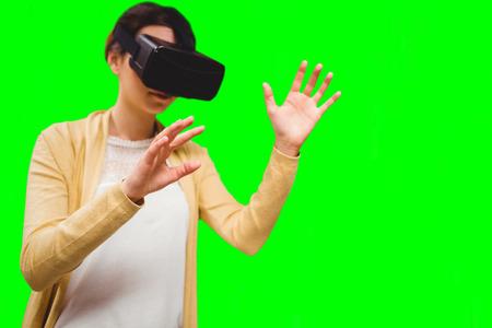 Businesswoman holding virtual glasses against green vignette Stock Photo