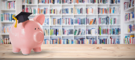 certificated: Piggy bank with graduation hat against teacher reading books to her students