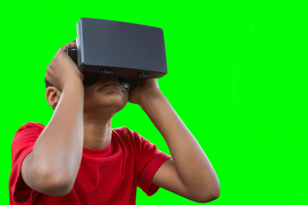 virtual reality simulator: Boy with virtual reality simulator against green vignette
